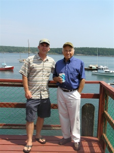 Tim Coates and Jeff Chouinard, co-owners of Real Cheap Sports stand on pier in Cundy's Harbor, Maine.